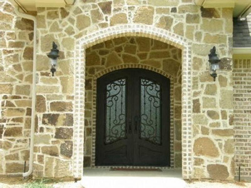 French Country Entry with Iron Doors and Brick and Stone